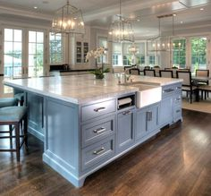 Large Kitchen Island and light fixture ideas and color scheme and layout Design with farmhouse sink, paper towel holder, Super White Quartzite Countertop and furniture-like cabinet. Kitchen Island East End Country Kitchens Farmhouse Kitchen Island, Kitchen Island Decor, Farmhouse Sinks, Kitchen Ideas, Kitchen Country, Kitchen Island With Sink And Dishwasher, Kitchen With Big Island, Kitchen Inspiration, Large Kitchen Island Designs
