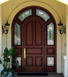 Solid wood door with custom archtop transom and sidelights.