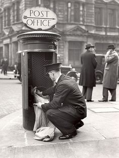Postman is clearing letters into sack from open pillar box. Sign on top of pillar box is pointing towards Post Office, 1936 Find this on our online catalogue London History, British History, Asian History, Tudor History, Black History, Old Pictures, Old Photos, Pen Pal, Post Bus