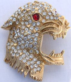 This is a wonderful gold toned brooch made in the form of a roaring leopard's head. The brooch is completely covered with clear rhinestone and the eyes of the cat are made of red glass stones. The bac