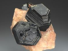 Phlogopite on Calcite, Arandis, Swakopmund, Erongo Region, Namibia. Pseudohexagonal lustrous black crystals up to 3cm displaying stepped habit prism faces, and terminations. On pinkish Calcite matrix.