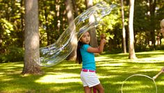 Child forming giant bubbles with homemade wand