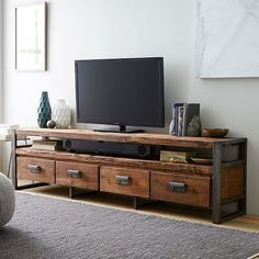 """Rustic and industrial. Iron legs and drawer pulls lend an industrial edge to the Bin Pull Media Console, which is crafted of reclaimed pine. Four roomy drawers provide plenty of storage space for DVDs, electronics and more. 82""""w x 16""""d x 22""""h. Reclaimed pine and iron"""