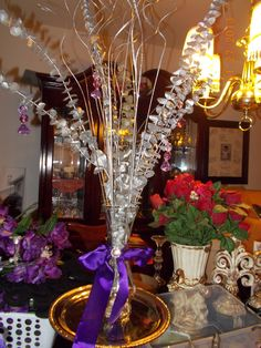 """I made this beautiful $5.00 arrangement using 2 dollar store eucaliptus branches and 2 other branches (curly) colored in silver. I also bought the """"beads"""" at the dollar store and put them together to hang them up from the branches. I put the branches in a dollar vase and embelished the vase with ribbon."""