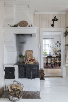 """M Y H O M E : Julförberedelser i återbruksstil. Vedspisen Bolinders från 1891 är nu fungerande sedan efter parets renovering. Här rullas och steks köttbullarna till jul. En viktig familjetradition är """"dopp i grytan"""" där spisringarna tas ur och en kopparkittel med skinkspad sätts över elden. Plåtlampan över dörren har hittats i uthusen och fått ny el indragen."""