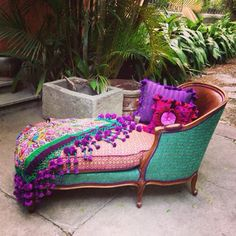 A chaise lounge like that needs lots of air and space. The bright colours,curved lines and violet pompoms work well here, because there are just enough neutral tones and geometric angles to set it off. The living border of greenery adds to the feeling of freshness and vibrancy.
