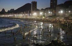 Poeple gather on the Copacabana beach Rio de Janeiro, Brazil - Mario Tama/Getty Images