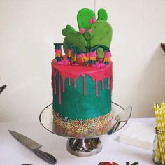 Mexican themed cactus drip cake with uno cake topper. (Teal and hot pink with sprinkles)