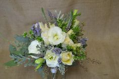 Bohemian white, green, and lavender bouquet made with roses, lisanthus, rosemary, lavender, ornamental oregano, seeded eucalyptus, veronica, and dusty miller. Fleurish Floral Designs