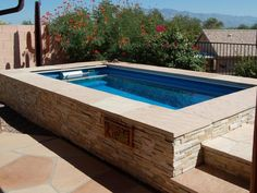 A stacked-stone encased lap pool by   Endless Pools  fits snugly on the corner of this Western terrace, leaving just enough room for a pop of color from surrounding vegetation.