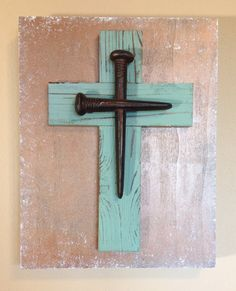"""Large wooden, triple layer, block wall cross. The block is painted with a bronze spray paint and distressed with white acrylic paint. The piece is then topped with a distressed teal wooden cross and accented with a rusted iron nail cross. Dimensions are approximately 11"""" x 14"""". Each cross is handmade with love and truly one of a kind."""