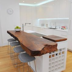 White kitchen cabinets, white floors, pendant lights, finished wood slab island - no sink in island