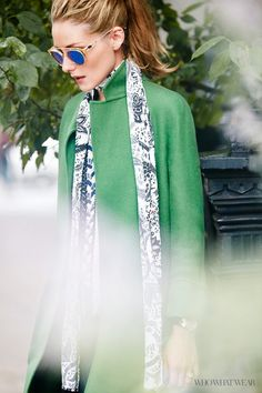 Olivia Palermo wears mirrored round sunglasses and a skinny scarf with a green coat. #TheStreeties