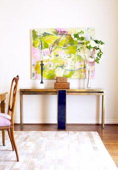 a gold console table and bright art work