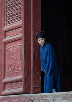Taoist nun looking out of temple. Photo by Raphael Bick.