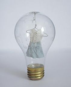 What better place for these miniature clothes than inside a lightbulb? They are made out of Japanese paper treated with konnyaku, hand-sewn with thread. The hangers are made of wire.