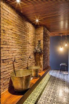 O despojamento do lavabo soma piso em ladrilho hidráulico e parede em tijolos de demolição com bancada em madeira e baldes de cobre fazendo as vezes de cubas