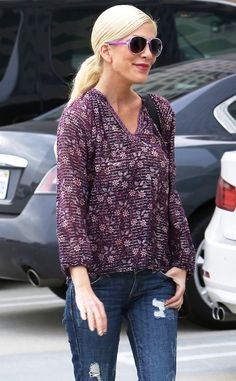 A smiley Tori Spelling stepped out in a flowing floral purple top, paired with matching aviator-inspired sunnies!