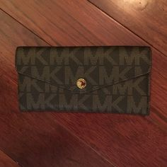 """Authentic Michael Kors wallet. NWOT. Authentic Michael Kors wallet. NWOT. Designed in the signature tone on tone logo-print jacquard with front button closure. Features a wealth of interior card slots (10) and pockets (2). Outside back slip pocket holds an extra zipper closed coin purse. Tried my best to take picture of one of the inner silicone tags which states """"Made in China E -1205"""" on both main wallet and coin purse. Michael Kors Bags Wallets"""