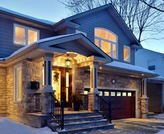 Award winning remodel of a split level  home features a complete exterior makeover with a new inviting front entry, stone with candel detailing, cement fibre siding, and a new roof overhang, which is both functional and aesthetically pleasing.