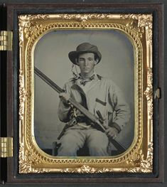 Soldier in Confederate pullover hunting-style shirt with dark military-type trim with double barrel shotgun, revolver, and side knife