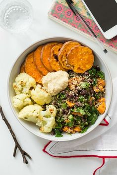 This lunch bowl is full of black beans, quinoa, roasted squash, cauliflower, and hummus.