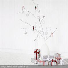 Schöne Weihnachtsdeko erhöht die Freude auf Weihnachten: Ein Zweig, verziert mit Weihnachtsbaumschmuck und schön verpackten Geschenken, ist eine tolle DIY-Bastelidee…
