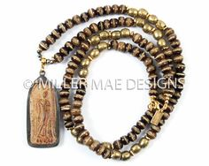 A beautiful antique Thai Buddha pendant is paired with mala beads from Nepal and brass beads from Ethiopia in this natural piece. Wear a symbol