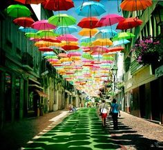 In Águeda, a small Portuguese town, some streets are decorated with colorful umbrellas that seem to magically float in mid-air, sheltering people on the streets below from the hot summer sun.