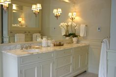 Pale sand walls paint color, white bathroom double vanity with double sinks, calcutta gold marble counter tops, orchid, wainscoting, and polished nickel faucets.