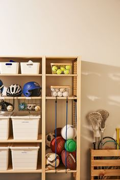 Get a barebones shelving unit that holds sturdy bins and baskets. Drill holes in two shelves to anchor bungee-cord hooks, stretch the cords between them, and stash balls inside. Back To School Organization, Home Organization, Organizing Tips, Organising, Kids Storage Units, Garage Storage Bins, Diy Storage Shelves, Kitchen Storage, Sports Equipment Storage