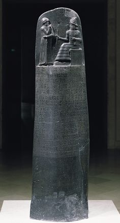 The Stele of Hammurabi, one of the first law codes of ancient times. Atop the Stele, we see an image of Hammurabi receiving the code from the Sun God.