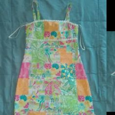 """Lilly Pulitzer Originals Dress Sz 0 Sleeveless Adorable Lilly Pulitzer dress in a size 0.  Adorable patchwork style pattern featuring tie accents at the bottom sides as shown in third picture.  Seam directly under bust measure 13.5"""" when laid flat.  Overall length of dress measures 26"""".  Excellent condition and from a smoke and pet free home. Lilly Pulitzer Dresses Mini"""