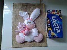Sacola em juta decorada com coelho feito de feltro branco e rosa. Ideal para quem gosta de presentear com caixas de bombom uma ótima opção de embalagem. A caixa de bombom não acompanha o produto é só uma demonstração do tamanho da embalagem. Pode ser feito na cor que quizer. R$ 15,00