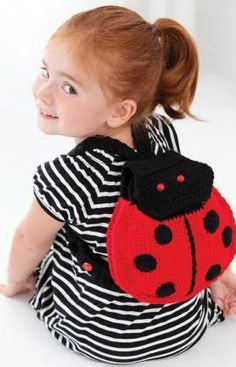 Your little lady will love carrying her special things in this unique back pack. Crocheted with machine wash and dry yarn, it's easy to keep it looking great no matter where it travels.
