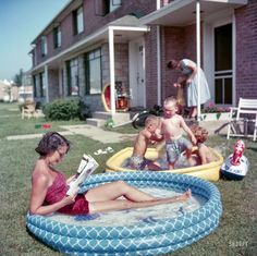From 1954, and a world away from Lana lounging: Woman relaxing in an inflatable swimming pool while her children play nearby in Park Forest, Illinois. Photos for a Look magazine assignment on life in suburbia.