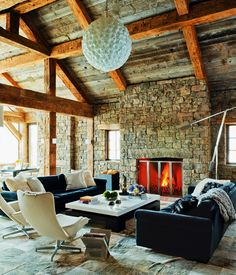 Interesting mix with the rustic stone and wood beams mixed with modern touches of light fixture and white chairs