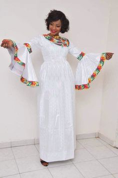 2 piece ankle length gathered white bazin riche with asymmetrical neckline, wide bell sleeves and multi colored embroidery. We suggest that you leave us your measurements to get a better fit. But if somehow you are unable to do your own measurements, then African Dresses For Women, African Print Dresses, African Print Fashion, Africa Fashion, African Attire, African Fashion Dresses, African Wear, African Women, Fashion Outfits