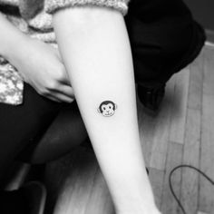 Small monkey emoji tattoo on the forearm. Tattoo artist: Jay...