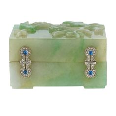 Art Deco Carved Jade, Platinum, Cabochon Sapphire and Diamond Box The square jade box carved with a bird perched on a blossoming tree, with stylized platinum buckle hinges and clasp set with rose-cut diamonds, centering 6 round cabochon sapphires, circa 1920