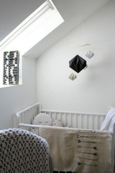 chambre de bébé blanche décorée d'un mobile lit bébé composé de diamants tridimensionnels en papier noir, gris et or
