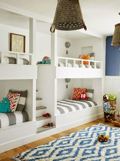 Fabulous boys' bedroom features white built-in bunk beds dressed in white and gray awning stripe duvet and shams flanking built-in steps alongside a white and blue diamond pattern rug illuminated by industrial bucket light pendants.