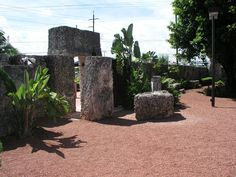 """Entrance to the Coral Castle. The tall rectangular piece of coral is from Florida City, and the coral creating the archway at the entrance is from Homestead. The 3 Ton Gate, which spins with the push of a finger, is to the right. The dolman or """"menhir"""" stone is in the distance to the right as well."""