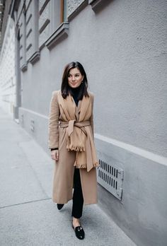 A tan coat and black distressed slim jeans feel perfectly suited for weekend activities of all kinds. For the maximum chicness pt for a pair of black leather loafers. Shop this look for $95: http://lookastic.com/women/looks/turtleneck-shawl-coat-skinny-jeans-loafers/7726 — Black Turtleneck — Tan Shawl — Camel Coat — Black Ripped Skinny Jeans — Black Leather Loafers