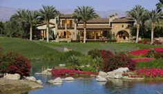 luxurious old world home with stone exterior, palm trees, large and lush backyard
