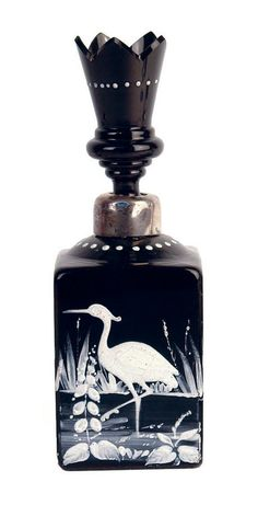 A Victorian black glass perfume bottle, the large square form bottle enamelled in the Mary Gregory manner with a heron in a river setting,