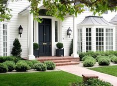 White exterior, bay window, black painted door, red brick path, boxwood