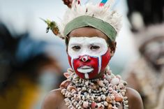 Boy wearing face paint and a big shell necklace. Eastern Highlands, Papua New Guinea.