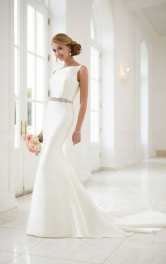 This modern keyhole back wedding dress by Stella York features a structured, fit-and-flare silhouette and high neckline for a fresh and updated bridal style. The Grand Mikado fabric gives off a sense of true elegance, while the long train give this otherwise simple wedding dress a hint of drama. Clean lines create a silhouette that elongates the body for a sleek and modern hourglass frame. The remarkable keyhole back adds just a wink of sexiness, as fabric covered buttons trail down the…