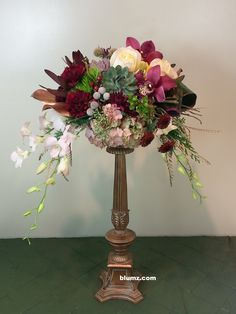 A raised centerpiece featuring the 2015 Pantone Color of the Year, Marsala. An antique gold candlestick serves at the lift for this floral design featuring blush roses, cymbidium orchid blooms, hydrangea, succulents, blush dendrobium orchids, and Merlot dianthus. Gold airbrushed foliages add a touch of regal elegance.